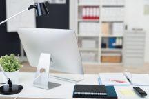 Arbeitsplatz mit Bildschirm und Unterlagen auf dem Tisch