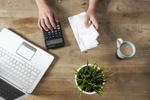 Blick von oben auf Hand mit Taschenrechner und Rechnungsbelegen, Kaffeetasse, Pflanze und Laptop auf Tisch