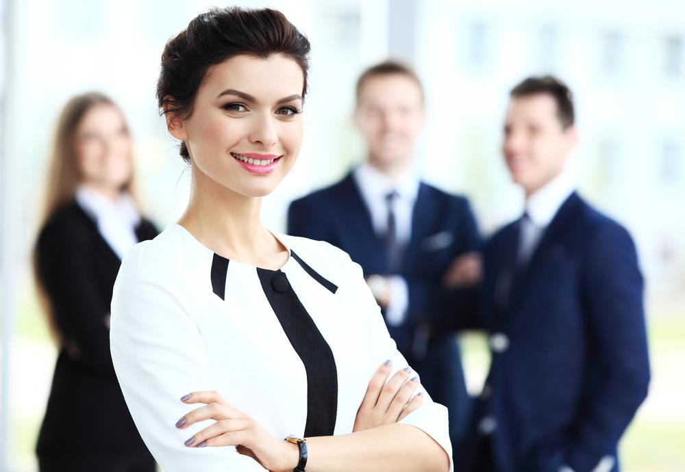 Junge Frau im weißen Blazer mit selbstbewusstem Gesichtsausdruck im Vordergrund und Mitarbeiterinnen und Mitarbeiter im Hintergrund