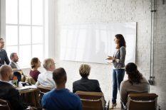 Gruppe von Erwachsenen, die einer Trainerin interessiert zuhören