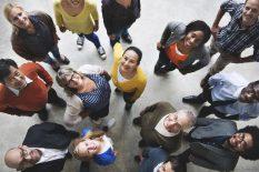 Gruppe von Menschen unterschiedlicher Herkunft und unterschiedlichen Alters, die in die Kamera schauen