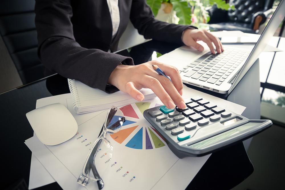 Hände einer Frau im Blazer mit einer Hand auf der Tastatur eines Laptops und einer Hand auf einem Taschenrechner