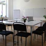 Seminarraum mit Tischen, Sessel, Flipchart und Whiteboards
