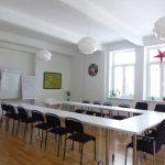 Lichtdurchfluteter Seminarraum mit Tischen und Sesseln im U aufgestellt