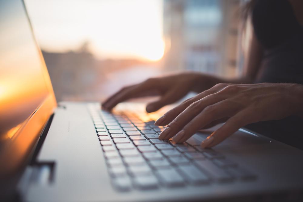Hände auf der Tastatur eines Laptops